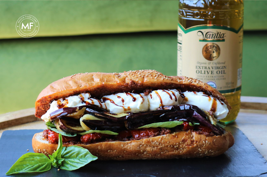 A filled-to-the-brim sandwich filled with eggplant, semi-fried tomato, and creamy burrata.